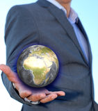 Young businessman holding earth. Young businessman holding in his hand a glowing earth globe Stock Image