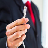 Young businessman holding an ethernet cable Royalty Free Stock Photos