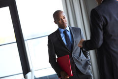 Young businessman holding file while listening to male colleague in office.  Stock Photos