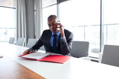 Young businessman holding file while talking on phone at conference table.  Stock Photography