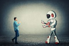 Fight against robot. Young businessman holding fists ready to fight against robot. Rivalry between human and technology. Danger of losing the job, replacing the stock photo