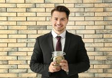 Young businessman holding glass jar with coins on brick background. Savings money concept royalty free stock image