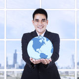 Young businessman holding a globe Royalty Free Stock Photo
