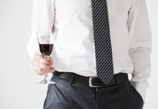 Young businessman holding a goblet of wine Royalty Free Stock Image