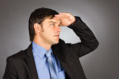 Young businessman holding his hand at forehead and looking forwa Stock Images