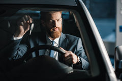 Young businessman holding key while sitting in new car Stock Images