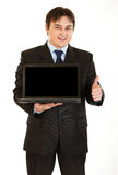 Young businessman holding laptop with blank screen Royalty Free Stock Photos