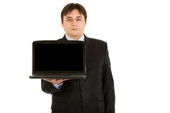 Young businessman holding laptop with blank screen Stock Photos