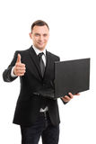 Young businessman holding a laptop giving a thumbs up. A portrait of a young businessman holding a laptop giving a thumbs up, isolated on white background Royalty Free Stock Photos