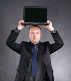 Young  businessman holding laptop on his head. On a gray background Royalty Free Stock Photo