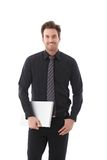 Young businessman holding laptop smiling Stock Image