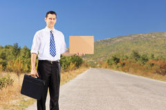 Young businessman holding a leather suitcase and hitchhiking. On an open road Royalty Free Stock Photos