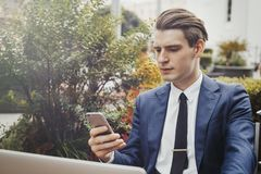 Young businessman holding mobile phone in hand and sitting next to green plant. stock images
