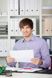 Young Businessman Holding Paper At Desk Stock Images