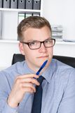 Young businessman is holding a pen at his chin Royalty Free Stock Image