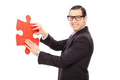 Young businessman holding piece of a puzzle Stock Images