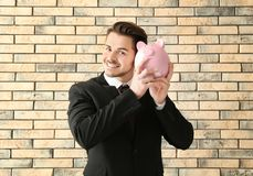 Young businessman holding piggy bank on brick background. Savings money concept royalty free stock photos
