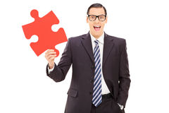 Young businessman holding a red piece of puzzle Stock Photo