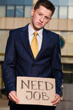 Young businessman holding sign Need Job outdoors. Financial crisis. Unemployment. Young businessman holding sign Need Job outdoors Royalty Free Stock Image