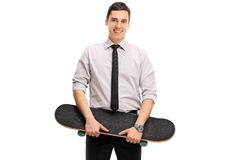 Young businessman holding a skateboard. Studio shot of a young businessman holding a skateboard and looking at the camera  on white background Stock Photo