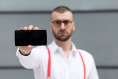 Young businessman holding smartphone. Selective focus and copy s. Young caucasian businessman holding smartphone. Selective focus and copy space Royalty Free Stock Photos