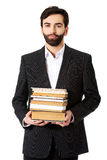 Young businessman holding stack of books. Stock Photography