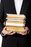 Young businessman holding stack of books. Stock Image