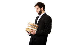 Young businessman holding stack of books. Stock Photo
