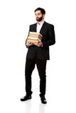 Young businessman holding stack of books. Royalty Free Stock Images