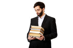 Young businessman holding stack of books. Royalty Free Stock Photos
