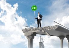 Young businessman holding street safety sign. Confident businessman in suit holding green go sign while standing on broken bridge with skyscape on background stock images