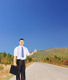 Young businessman holding a suitcase and hitchhiking on a road. Young businessperson holding a leather suitcase and hitchhiking on an open road, shot with a tilt Stock Image