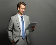Young businessman holding a tablet and the other hand in pocket Royalty Free Stock Images