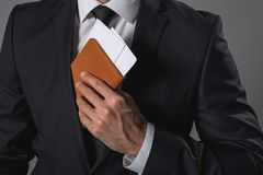 Young businessman holding tickets in hand. Close up of male arm putting two travel documents in inner right jacket pocket Stock Image