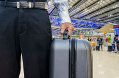 Young businessman holding a travel bag, in an airport Royalty Free Stock Image