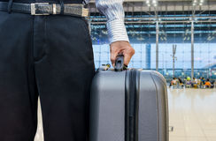 Young businessman holding a travel bag, in an airport Stock Photos