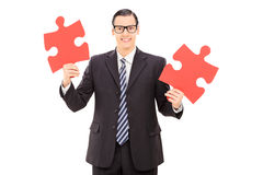 Young businessman holding two pieces of puzzle Stock Image