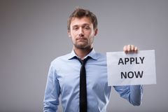 Young businessman holding up an Apply Now sign. Looking at the camera with a serious expression over grey Royalty Free Stock Photography