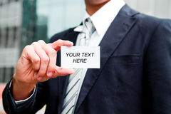 Young businessman holding visit card in hand Royalty Free Stock Images
