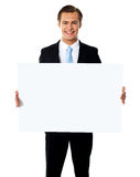 Young businessman holding white blank billboard Royalty Free Stock Images