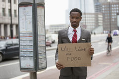 Young businessman holding Will Work for Food sign at street royalty free stock photos