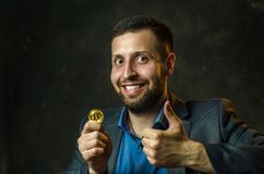 A young businessman holds a coin of bitcoite in his hand royalty free stock images