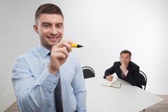 Young businessman holds marker writing, drawing Royalty Free Stock Image
