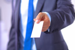 Young businessman holds out his hand with a business card Royalty Free Stock Images
