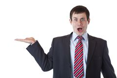 Young businessman holds surprised blank palm Royalty Free Stock Image