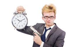 Young businessman holidng gun and alarm clock Royalty Free Stock Photos