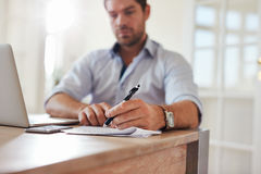 Young businessman at home office signing documents. Shot of young businessman sitting at home office with laptop and signing documents. Young man working from royalty free stock images