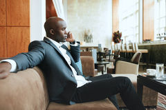 Young businessman at hotel lobby making a phone call Royalty Free Stock Photos