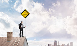 Young businessman on house brick roof holding yellow signboard and looking at city. Mixed media Stock Image