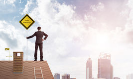 Young businessman on house brick roof holding yellow signboard and looking at city. Mixed media Stock Photography